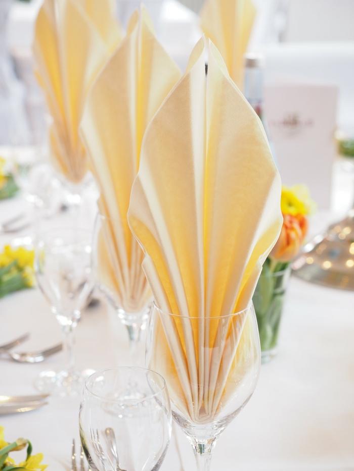 orange Servietten Kommunion, kleine Tulpen in Vasen, weiße Tischdecke