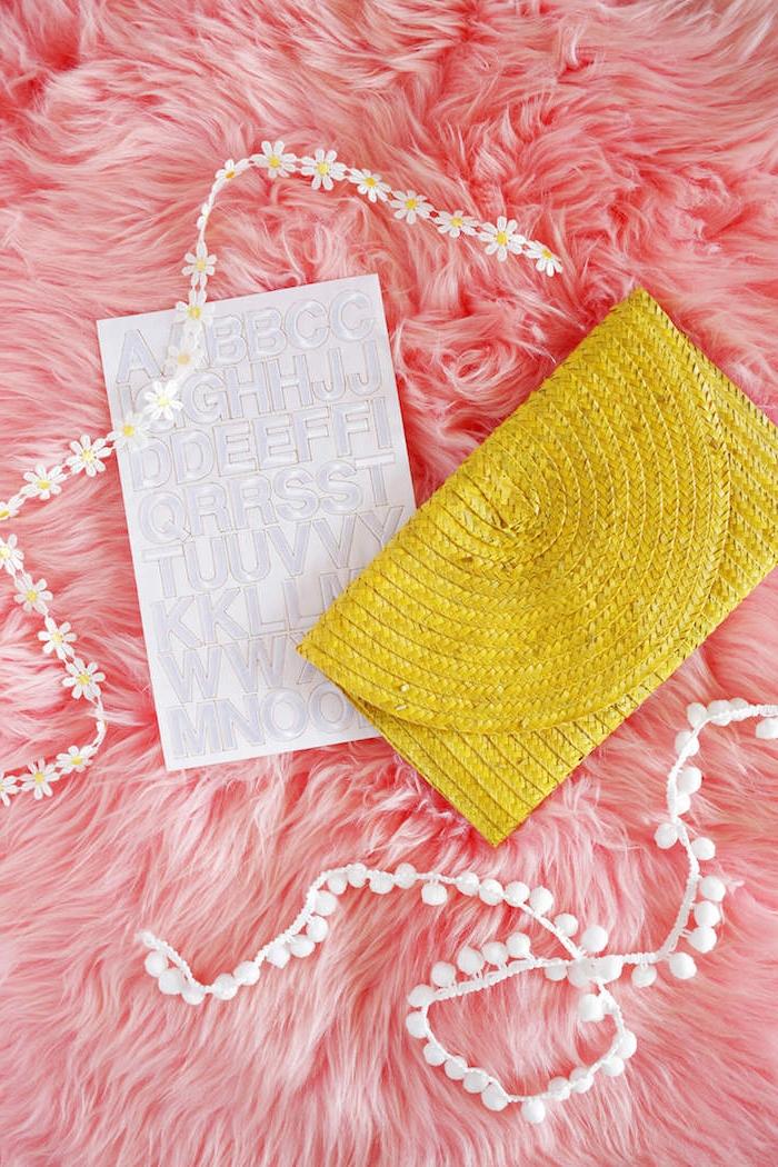 Gelbe Clutch selbst verzieren, mit weißen Pompons, kleinen Blumen und Buchstaben