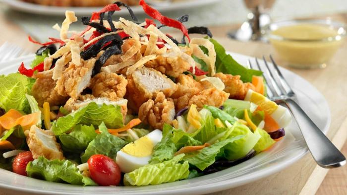 Gesunde Salate, grüner Salat, paniertes Hähnchenfillet, gekochte Eier,