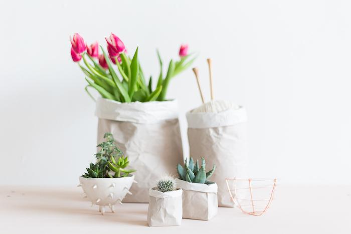 eine weiße wand und ein weißer tisch, klöeine und große blumentöpfe mit weißen papiertüten und mit violetten blumen mit grünen blöttern, einem weißen faden udn kleinen grünen kakteen