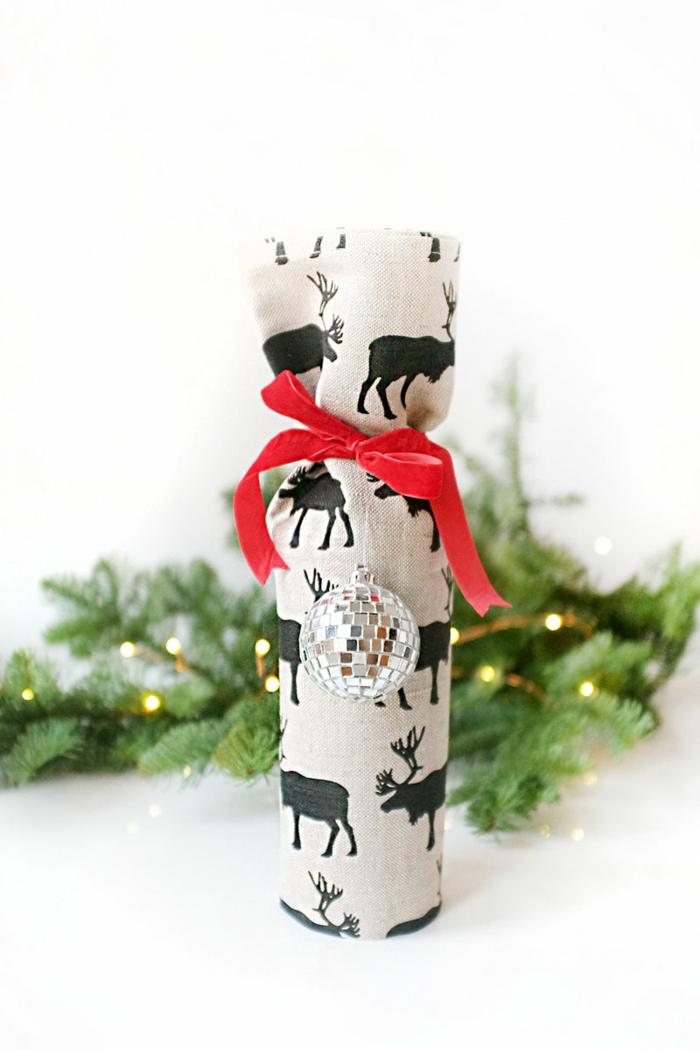 eine kleine Flasche mit silbernem Kugel und rote Schleife, Flasche als Geschenk verpacken