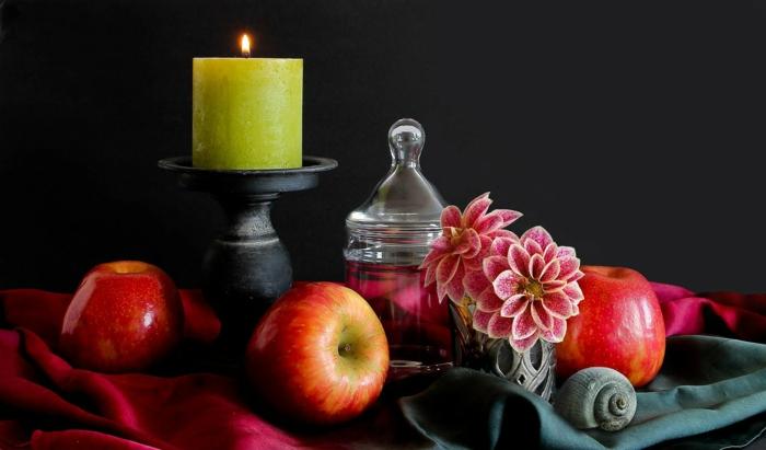 eine gelbe Kerze, kleine Äpfel, eine Vase mit rosa Blumen, Tischdeko Kommunion