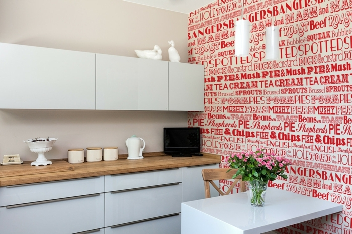 rote Aufschriften, weiße Regale, Wandtattoo Küche, rosa Blumen auf dem Tisch