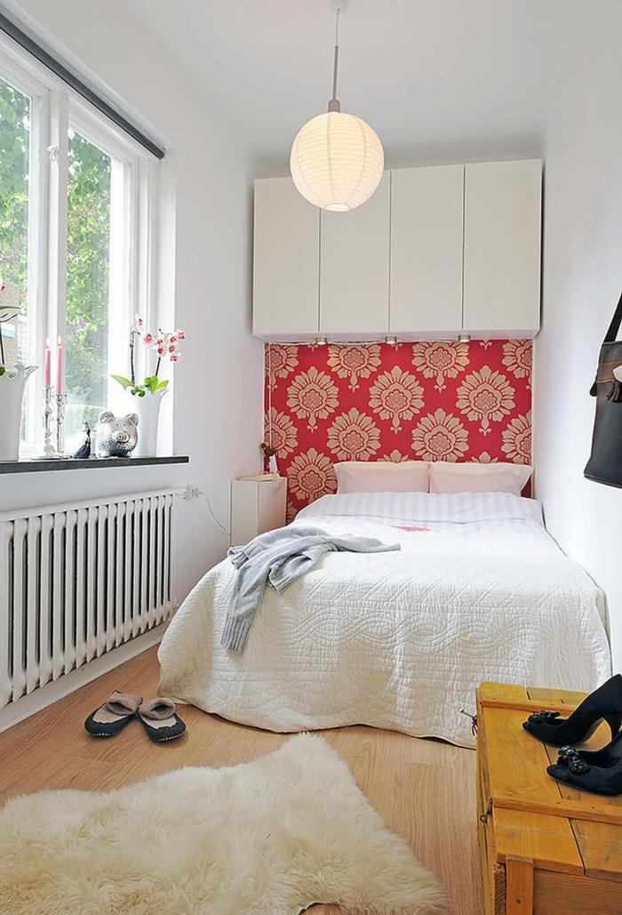 ein kleines Schlafzimmer für zwei, ein weißes Bett, rote Tapete mit Blumenmuster, kleine Räume optisch größer wirken