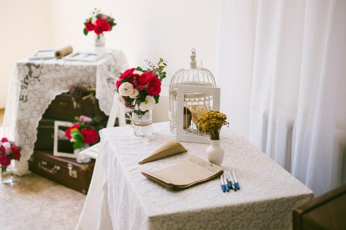 kleine Vase mit Blumen, ein weißer Käfig, weiße Decke mit Blumenmuster, Tischdekoration Kommunion