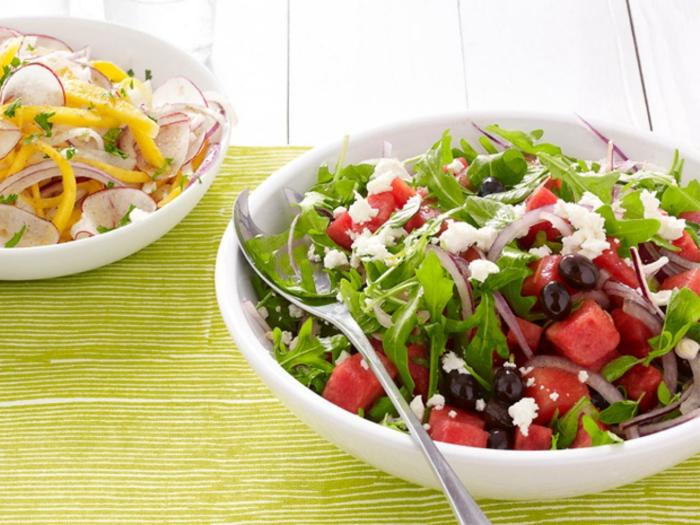 Rucola, rotes Gemüse, Oliven, Käse, gesunde Salate in einer weißen Schale