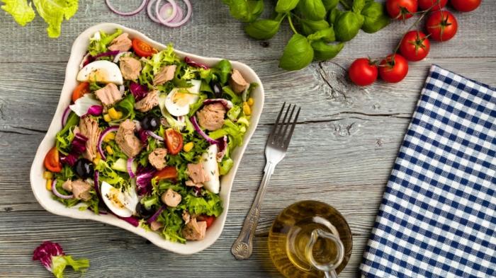 schnelle Salate von Eier und Fleisch mit Gemüse in quadratem Teller