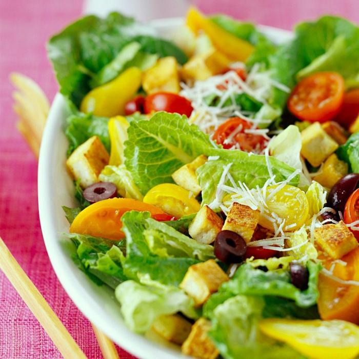 Croutons, grüner Salat, gelbe und rote Kirschtomate, geriebener Käse, gesunde Salate