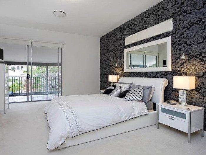 bett deko, weiße bettwäsche mit silbernen dekorationen, graue kissen, schwarze wand mit grauen elementen