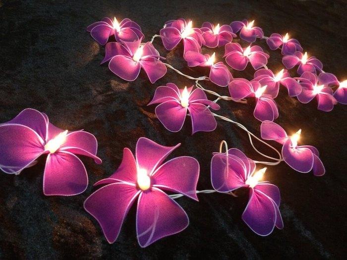 schöne schlafzimmer mit lichtketten in der form von blumen gestalten und dekorieren, lila glühlampen