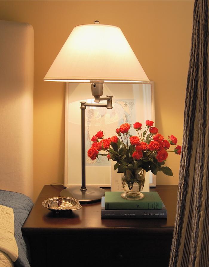 schlafzimmer dekorieren, neben dem bett soll ein kleiner schrank stehen, bücher darauf, frische rosen, lampe