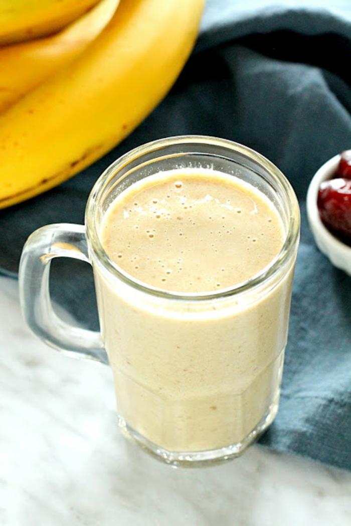 smoothie rezept, kohlenhydratefreies essen, bananen im hintergrund und ein glas mit eiweißshake im vordergrund