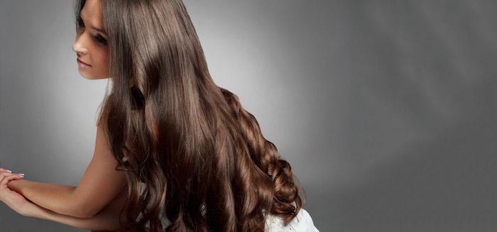 schnelleres haarwachstum, lockhaarfrisur, frau mit langen haaren, haarfarbe mahagoni, grauer hintergrund