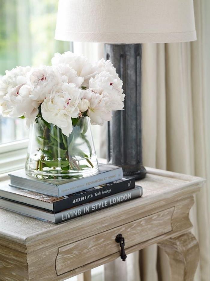 schlafzimmer modern gestalten, idee für gemütliches flair zu hause, weiße blumen vom garten in vase auf den büchern stehen, schrank mit schublade