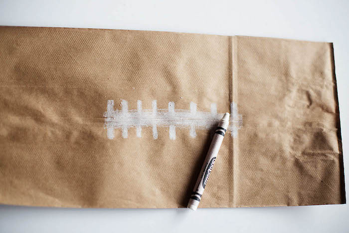 eine kleine braune papiertüte und ein weißes pastell und ein weißer tisch, eine anleitung, einen ball aus einer papiertüte selber machen