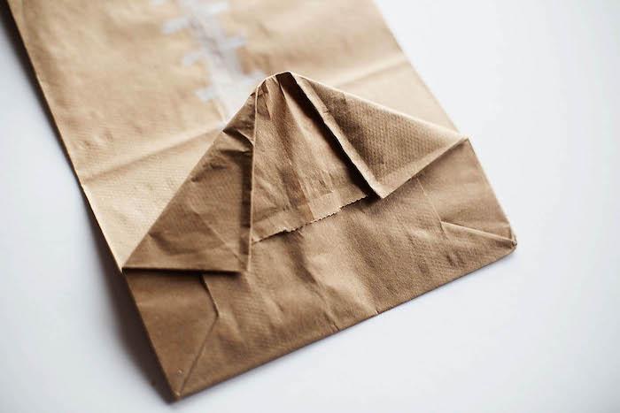 eine kleine braune papiertüte falten und ein weißer tisch, eine diy anleitung, basteln mit papier, einen ball aus papier selber machen
