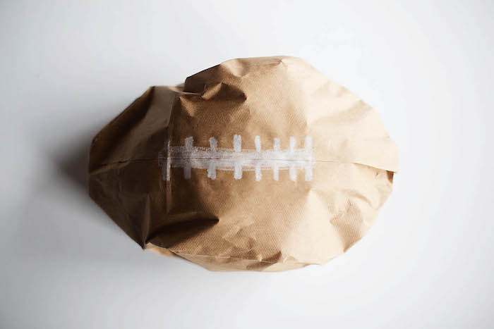 ein weißer tisch und ein kleiner brauner selbstgebastelter ball aus einer kleinen braunen alten papiertüte, basteln mit papier, einen ball selber machen diy anleitung