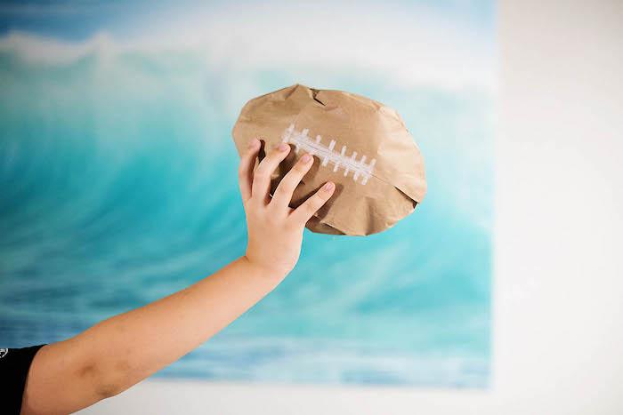 ein bild mit einem blauen himmel und mit einem meer mit großen blauen wellen, eine hand mit einem braunen ball aus einer alten braunen papiertüte