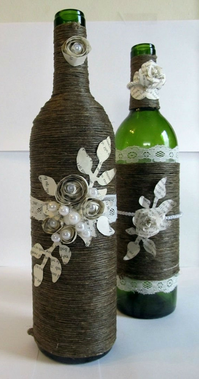 zwei Flaschen mit Ornamenten als Dekoration, kleine Blumen aus Papier und Spitze, Flasche einpacken