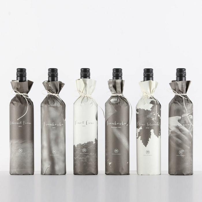 eine Reihe aus verpackten Flaschen in Grau und Weiß mit Muster versehen, Flasche einpacken