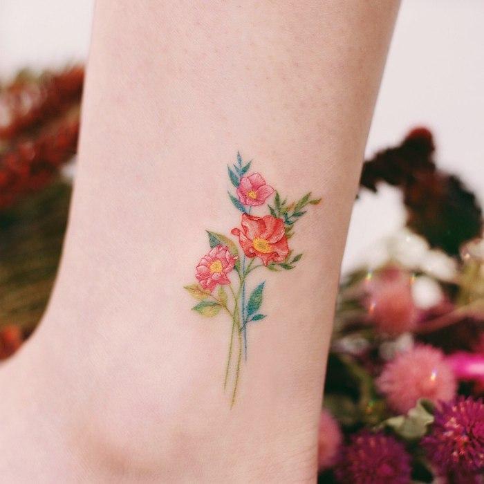 Kleines Tattoo am Bein, drei rote Blumen, kleiner Blumenstrauß, farbiges Tattoo