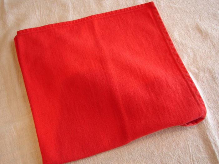 eine weiße decke und eine kleine rote serviette, eine bestecktasche falten, eine tischdekoration selber basteln