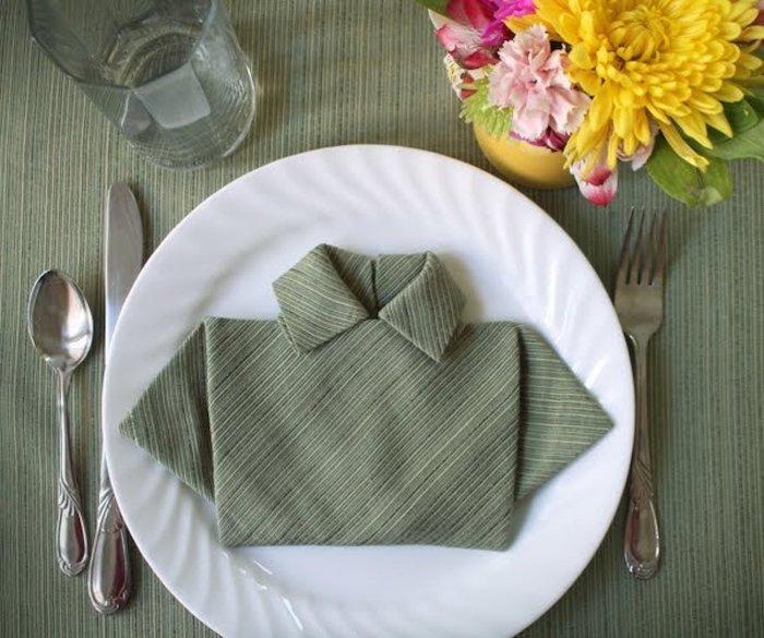 ein weißer teller und eine grüne serviette, gelbe und violette blumen mit grünen blättern, ein glas und ein messer, eine gabel und ein löffel aus metall und eine grüne decke