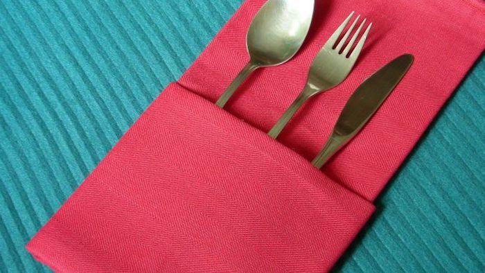 eone blaue decke und eine rote gefaltete bestecktasche mit einem messer, einer gabel und einem löffel aus metall, tischdeko selber basteln, bestecktaschen falten anleitung
