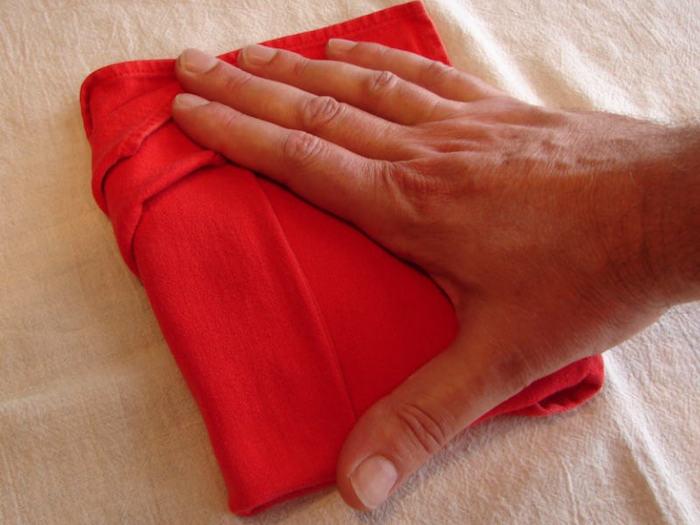 eine hand mit einer kleinen roten gefalteten serviette und eine weiße decke, servietten falten anleitung