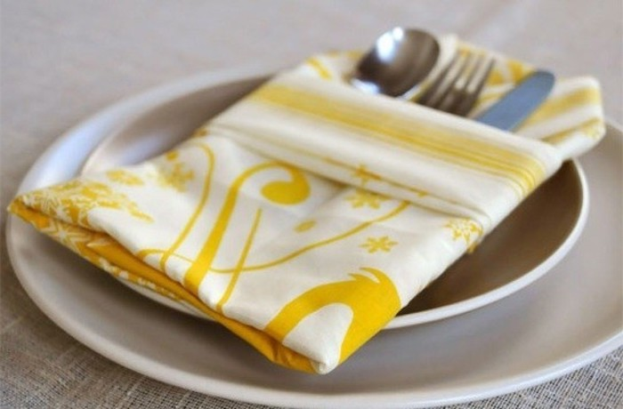 ein tisch mit zwei großen weißen tellern mit einer gefalteten gelben serviette, eine bestectasche mit einem messer, einer gabel und einem löffel, tischdeko selber machen
