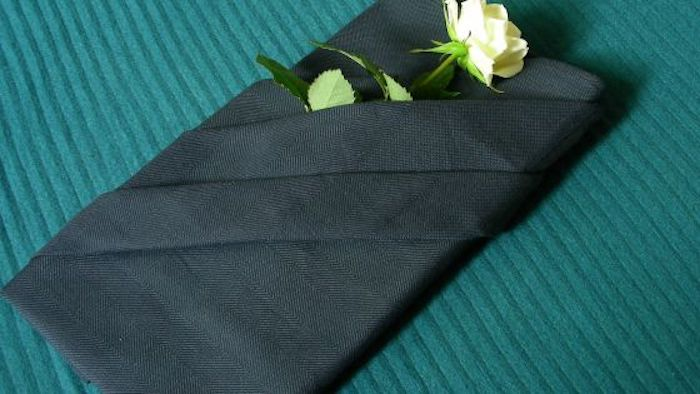 ein tisch mit einer grünen decke und mit einer großen schwarzen gefalteten serviette, eine schwarze bestecktasche mit einer weißen rose mit grünen blättern