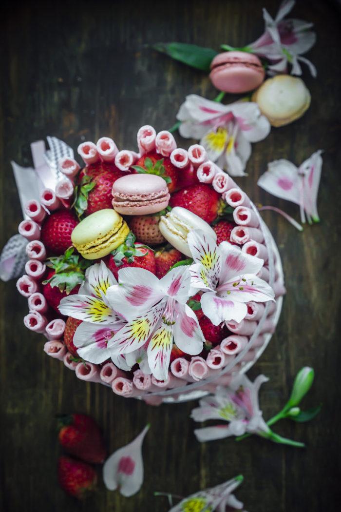 Tortendekoration aus Erdbeeren Lilien und französischen Macarons