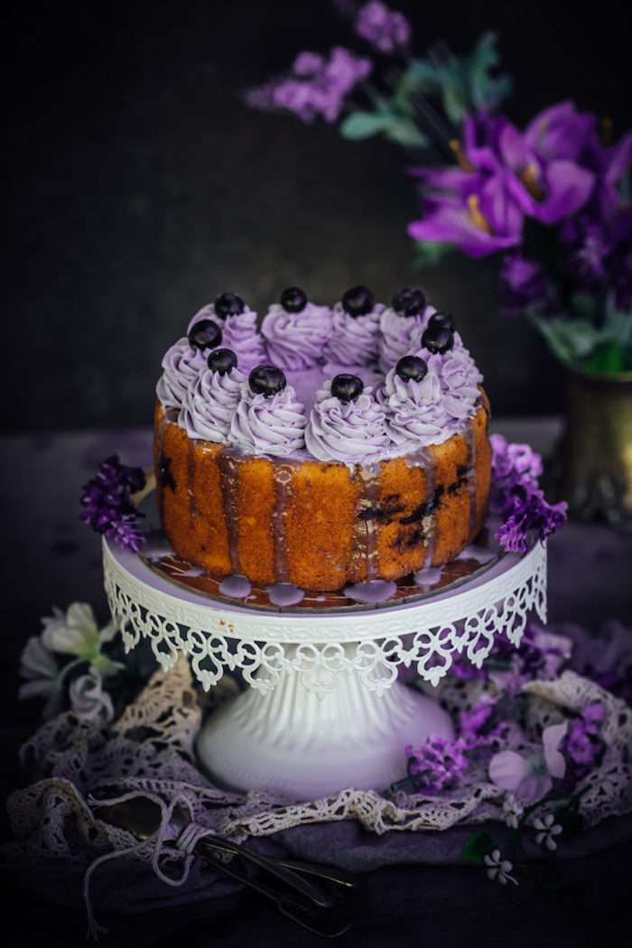Geburtstagstorte mit lila Creme und Blaubeeren, Spitze und lila Blumen