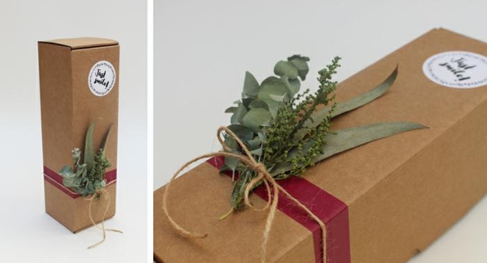 braune Flascheverpackung, ein Schleife, die ein paar Blätter befestigt, eine runde Aufkleber