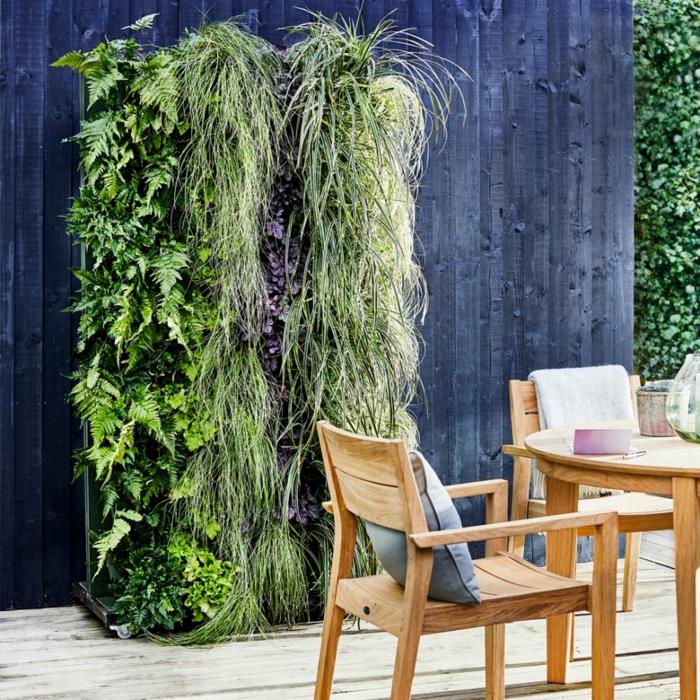 Stühle und Tisch aus Holz, ein vertikaler Garten mit Kletterpflanten an blauer Mauer, Terrassendiele