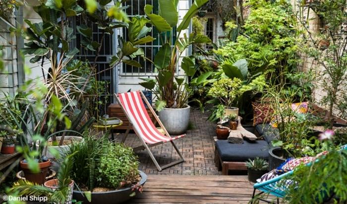ein gemütlicher Garten mit gestreifter Liegestuhl, kleine Fliesen und viele Pflanzkübel