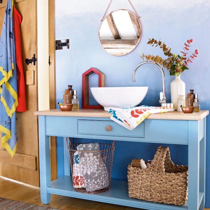 Badezimmer in Blau-Nuancen, weißes Waschbecken, Rattankorb und Badeaccessoires