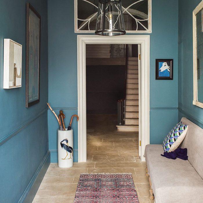 Flur in Blau, Sofa und Fliesen in Beige, weiße Tür, Bilder an der Wand