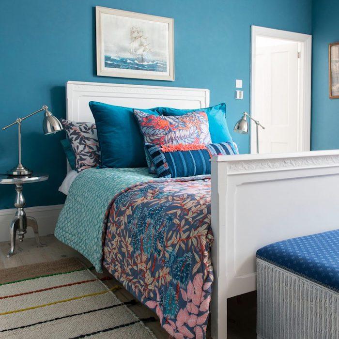 Wandfarbe Blau, weiße Möbel, Kissen und Bettwäsche mit Blumenmuster