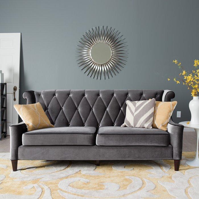 wandfarbe hellgrau mit einem schönen spiegel als deko, großes graues samt sofa mit kissen zum dekorieren und gelbe blumen in weißer vase