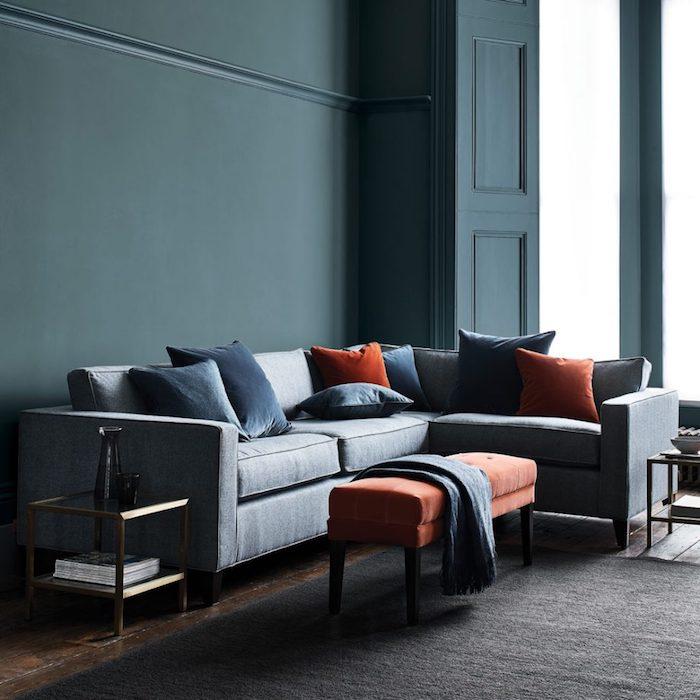 Wandfarbe Petrol, graues Sofa mit vielen Deko Kissen, Wohnzimmer Einrichtung in dunkeln Farbnuancen