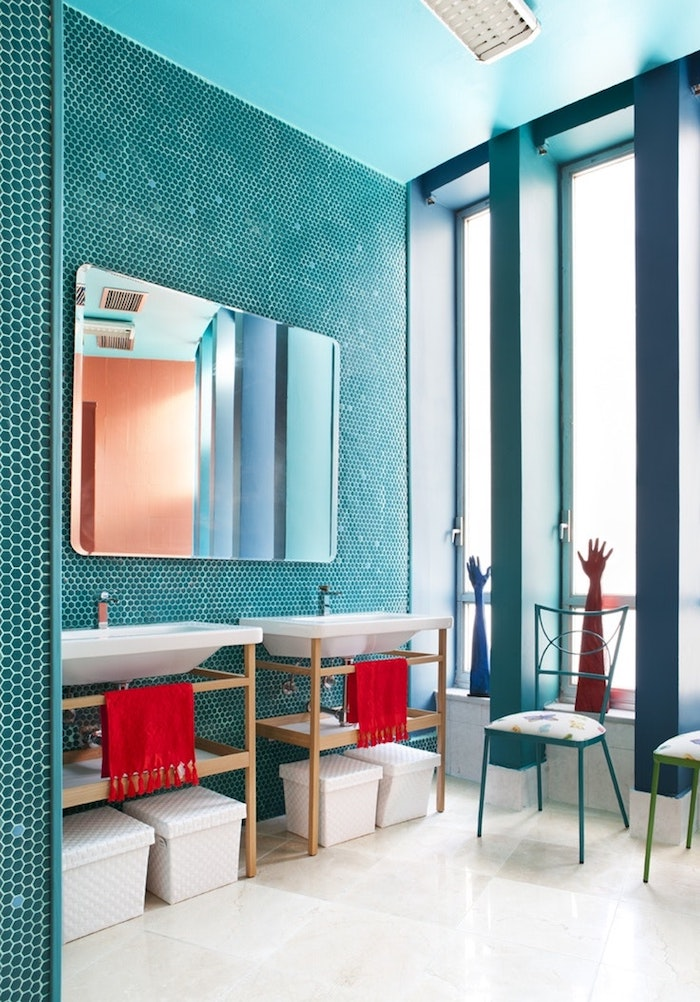 Badezimmer in Türkis, großer Spiegel, weiße Waschbecken, rote Tücher