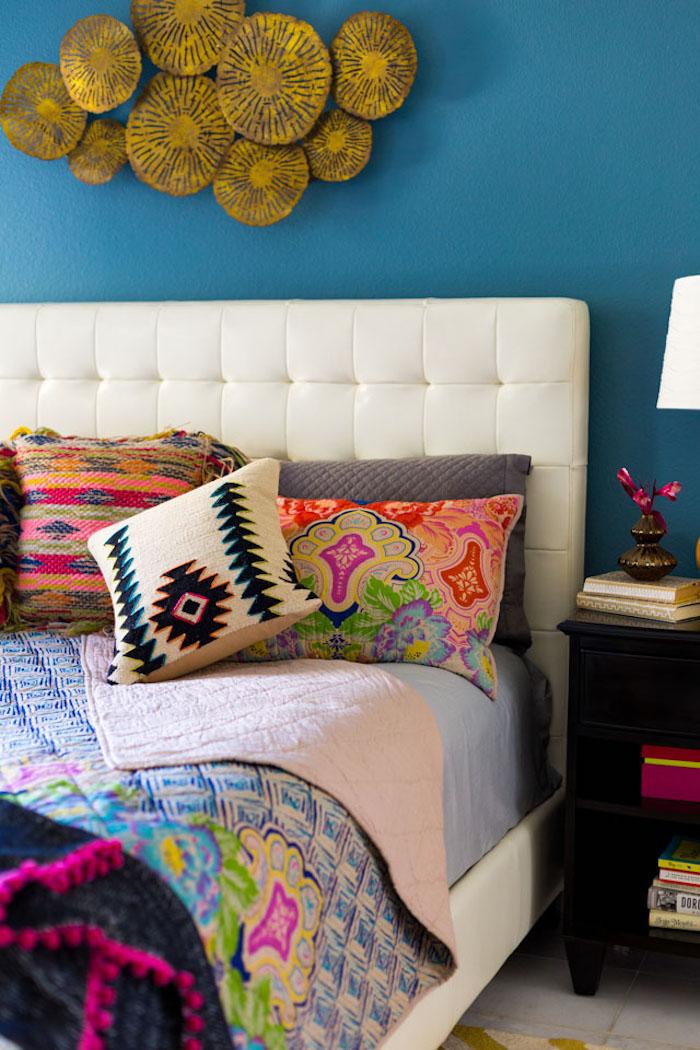 Schlafzimmer Gestaltung, weißes Bett mit bunten Kissen und Decke, Wandfarbe Blau