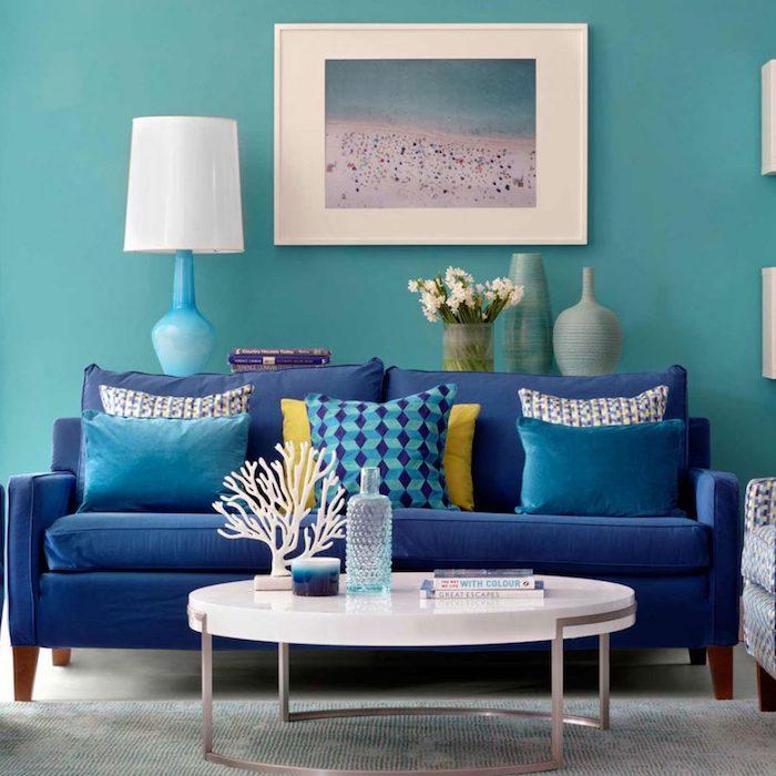 Wohnzimmer Einrichtung in Blautönen, Wandfarbe Türkis, dunkelblaues Sofa, weißer runder Couchtisch