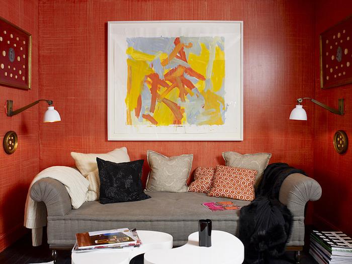 Wohnzimmer in Rot, graues Sofa mit vielen Deko Kissen, Gemälde und Wandlampen