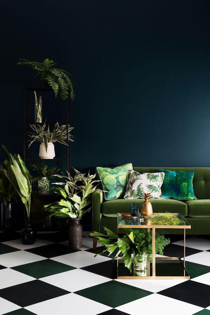 Wohnzimmer in dunklen Farben, Wandfarbe Schwarz, grünes Sofa, drei Deko Kissen, grüne Zimmerpflanzen