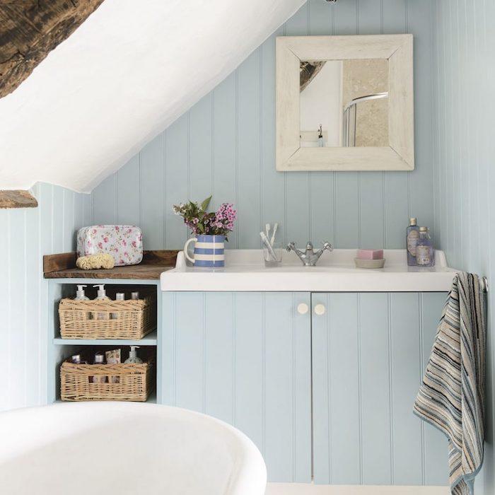 Badezimmer Einrichtung in Hellblau, Spiegel in weißem Rahmen, Rattan Körbe