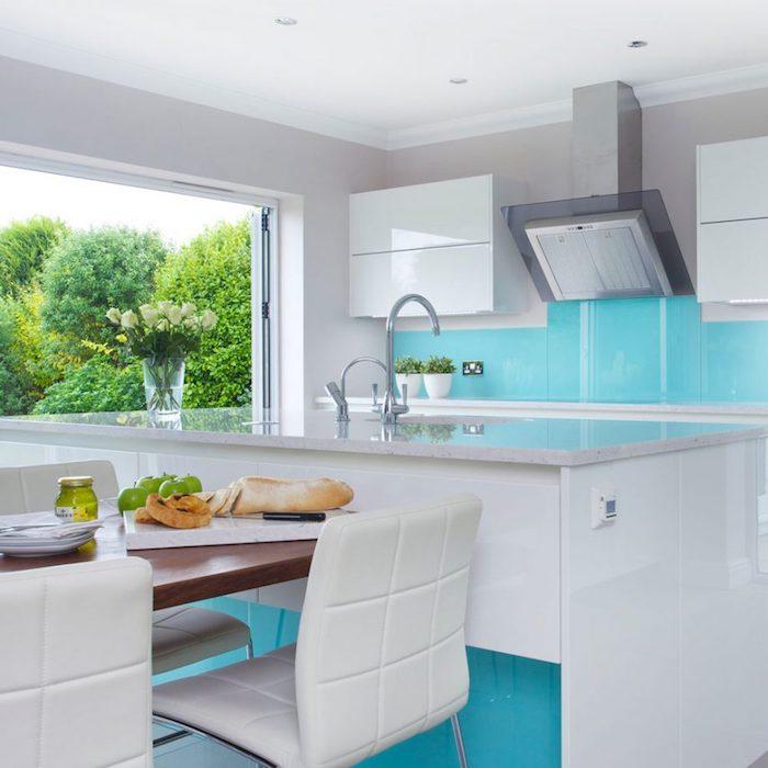 Kücheneinrichtung Inspiration, Fliesen in Weiß und Türkis, Rosenstrauß in GLasvase, weiße Lederstühle und Holztisch