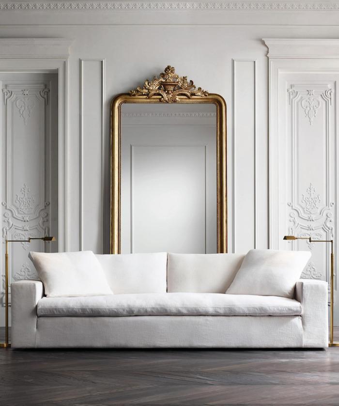 Wandfarbe Weiß, großer Spiegel mit goldenem Rahmen, weißes Sofa und Stehlampen