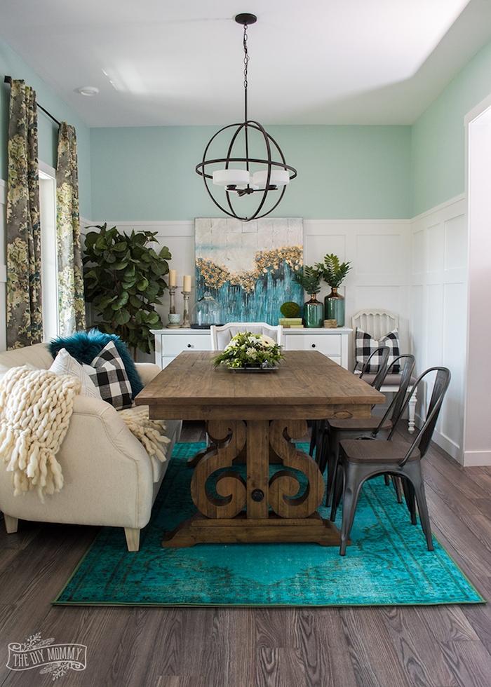 Wohnzimmer im Landhausstil, Tisch aus Massivholz, runder Kronleuchter, grüne Zimmerpflanzen, Kombination aus Blaugrün und Weiß